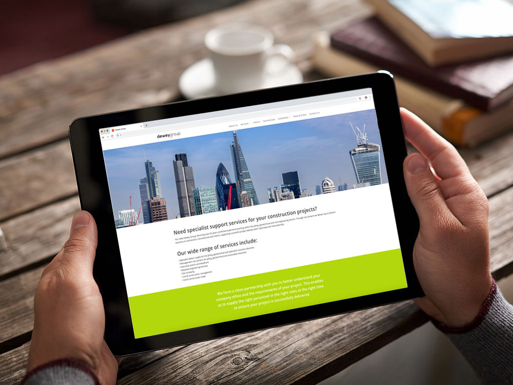 website design view on ipad London skyline with cranes home page for Dewey Group creative work website design and marketing