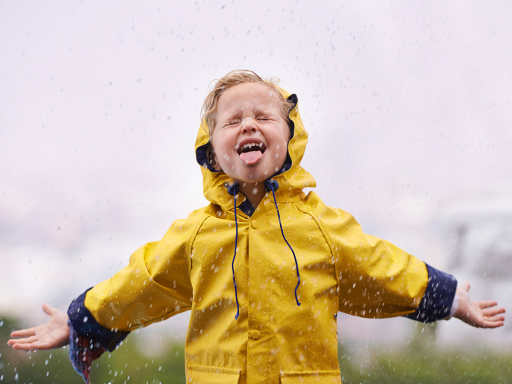 young girl in yellow raincoat embracing rain design & marketing news innovative creative ideas